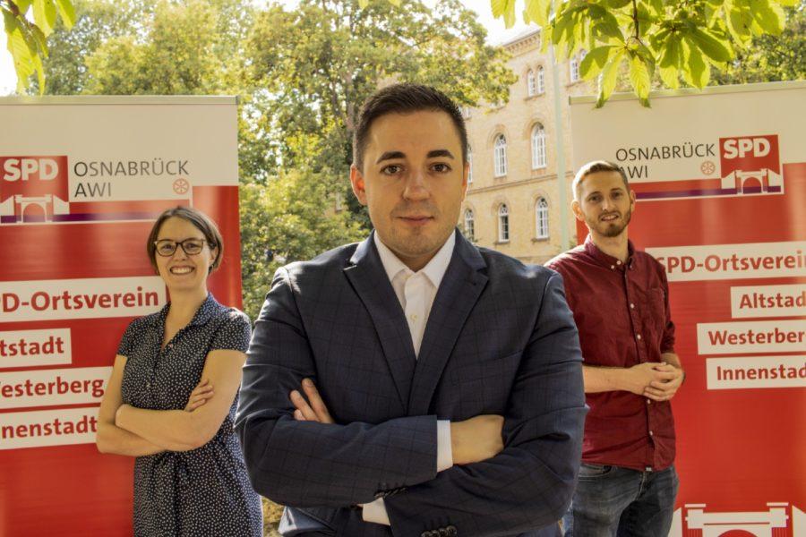 Manuel Gava steht in der Mitte von Lina Menke und Pascal Speicher. Hinter ihnen stehen SPD Aufsteller.